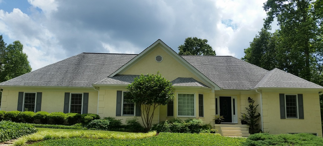 Here is a grey shingle roof in Sharpsburg, Ga covered with black stains.