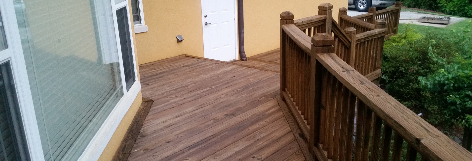 Honey gold wood stain applied to wood deck after deck pressure washing.