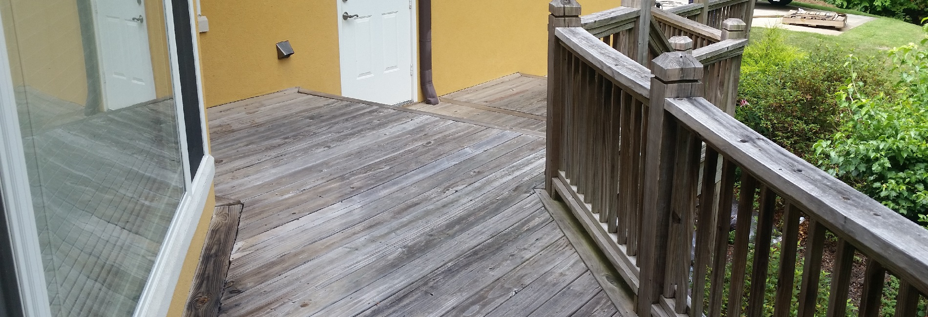 A deck this has weathered and lost it appearance due to lack of deck staining. Deck pressure washing can remove these grey fibers.