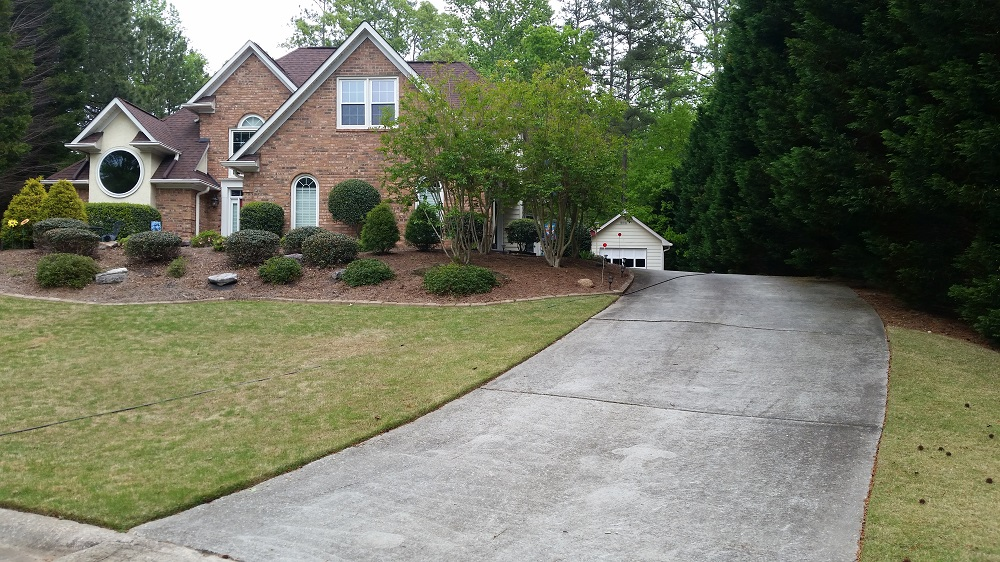 This a driveway with black mildew stains in Peachtree City, Ga